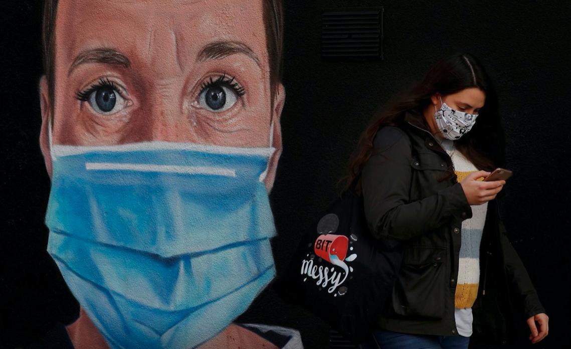 El estudio SIREN involucra a decenas de miles de trabajadores de la salud en Gran Bretaña Una mujer usa barbijo mientras pasa junto a un mural de una enfermera después del brote de la enfermedad por COVID-19 en Manchester, Gran Bretaña, el 11 de octubre de 2020. Archivo REUTERS / Phil Noble